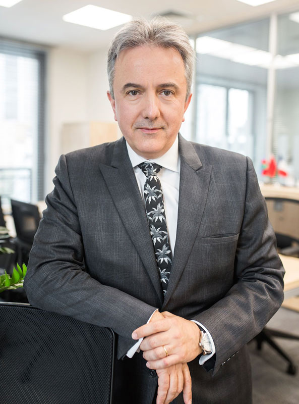 Francis Malige Of EBRD Posing For Photograph In Office Wearing A Business Suit