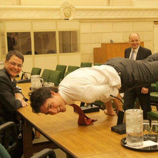 Justin Trudeau Smiling And Doing Yoga Pose On Table At Work In Front of Colleagues