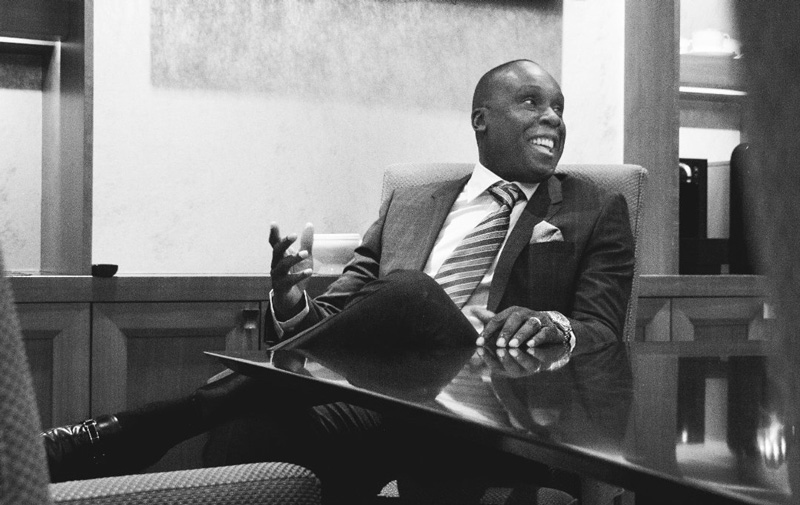 Bruny Surin Sitting At Desk In Business Suit And Smiling