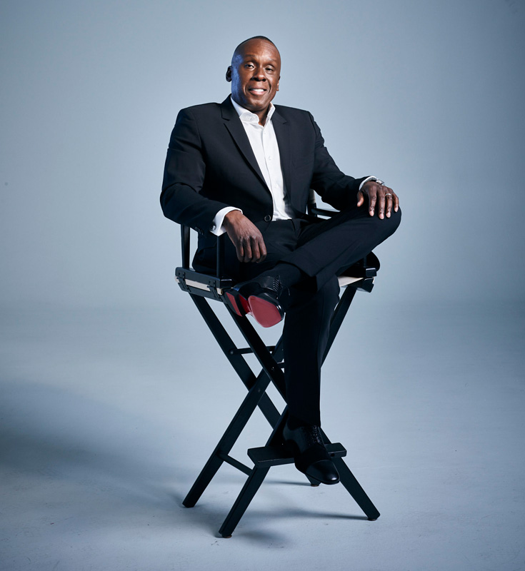 Bruny Surin Sitting In Directors Chair In Business Suit Looking Confident