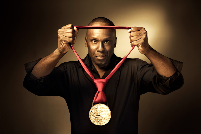 Bruny Surin holding Olympic Gold Medal