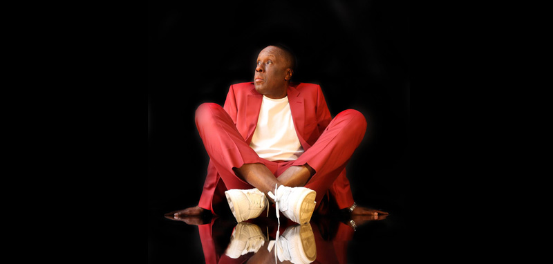 Bruny Surin Sitting Down Posing In Stylish Red Suit