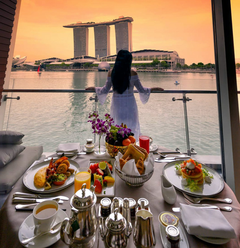 Woman Having Breakfast On Balcony Overlooking Marina Bay From her Hotel Room At The Fullerton Bay Hotel Singapore