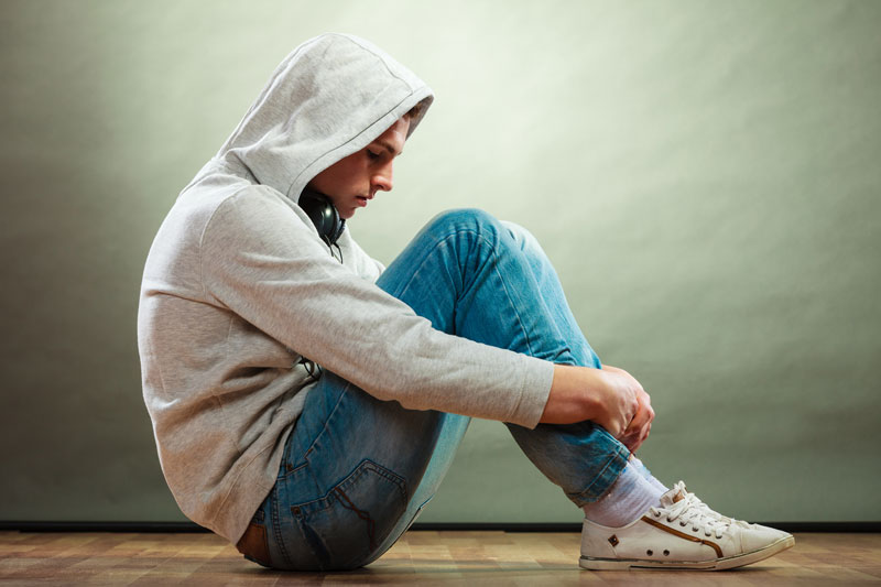 Teenager Sitting In Crouched Position Looking Sad