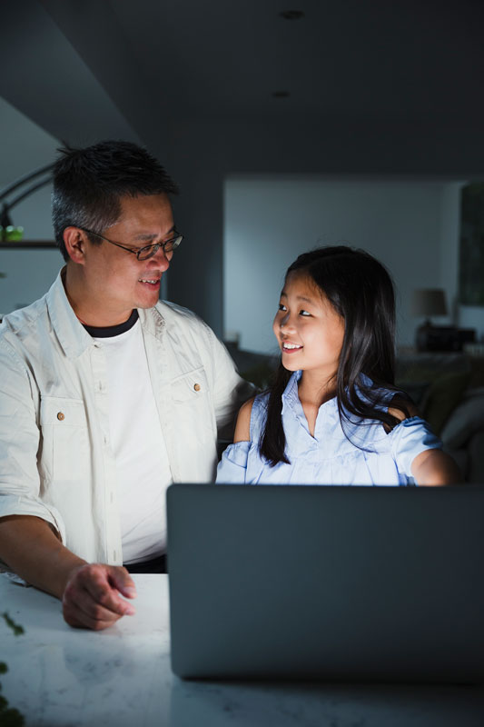 Smiling Asian Father Helping Young Daughter With A Computer