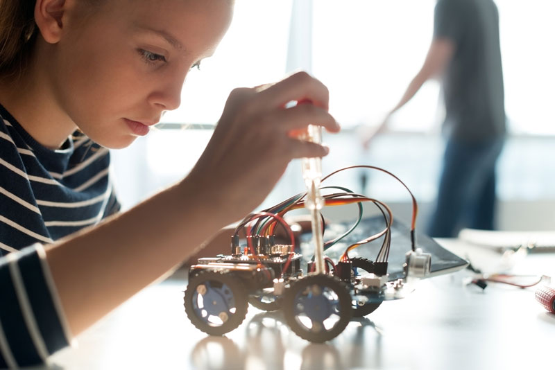 Teenage Girl With Screwdriver Making An Adjustment To A Small Robotic Vehicle
