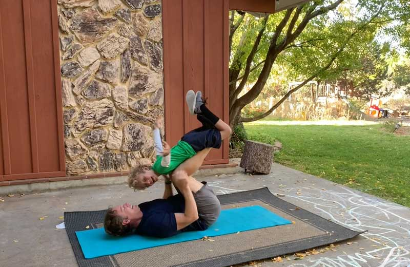 Sorren Harrison Of Fit Daddy 365 Doing 5 Lying Leg Lifts With Son On Laying On His Legs