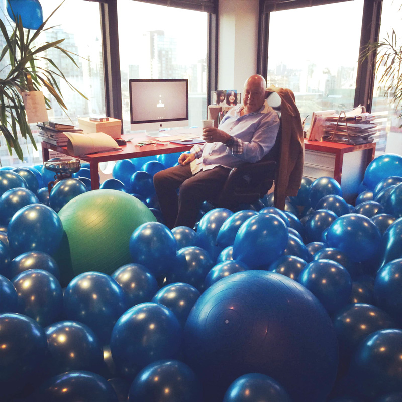Frank Palmer Sitting In His Office Filled With Blue Balloons