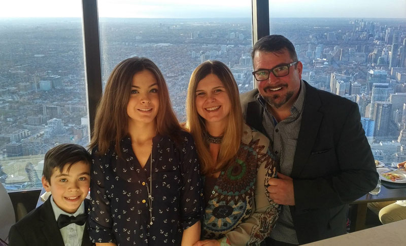 John Vellinga And His Family Posing For Photograph Overlooking City Of Toronto Canada From CN Tower