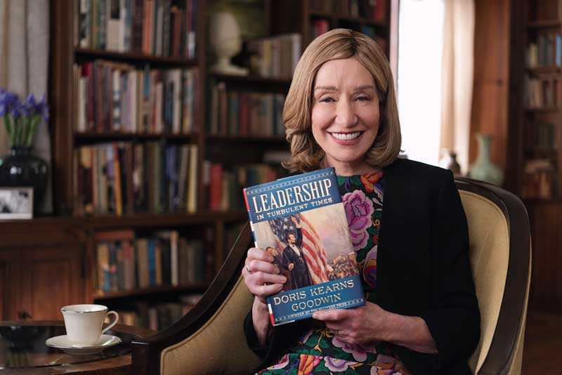 Doris Kearns Sitting On Chair Smiling And Holding Book Leadership In Turbulent Times