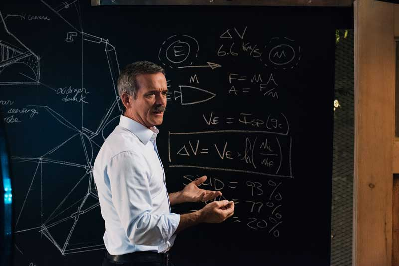 Astronaut Chris Hadfield Speaking In Front of Blackboard With Equations