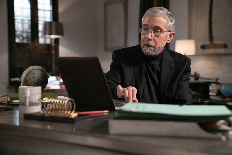 Economist Paul Krugman Sitting At Desk Working On Computer