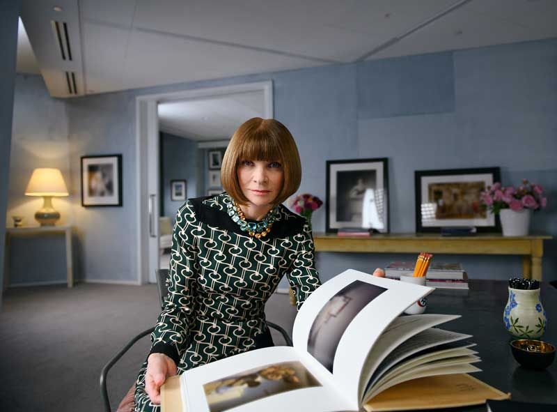 Fashion Guru Anna Wintour Holding Open Book While Seated In Her Office