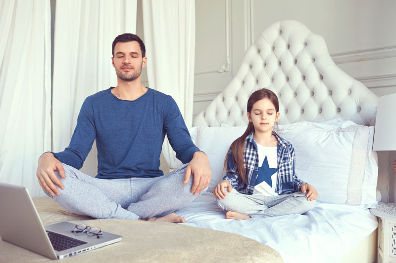 Father Daughter Sitting On Bed Meditating