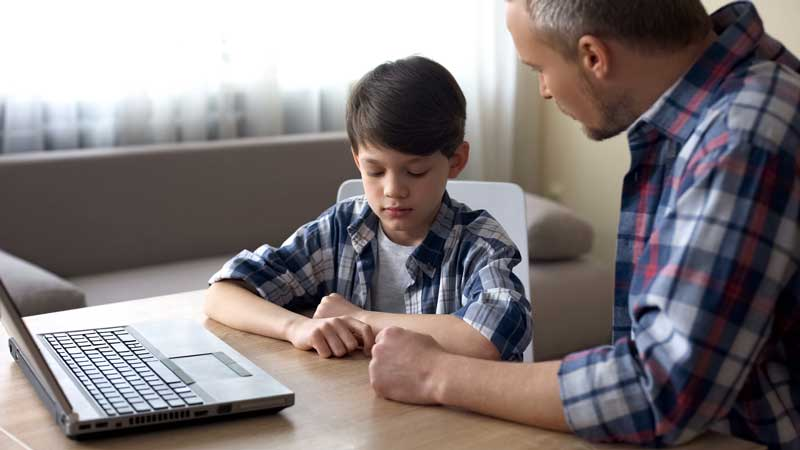 Father Talking To Son Who Seems Sad In Front Of A Computer