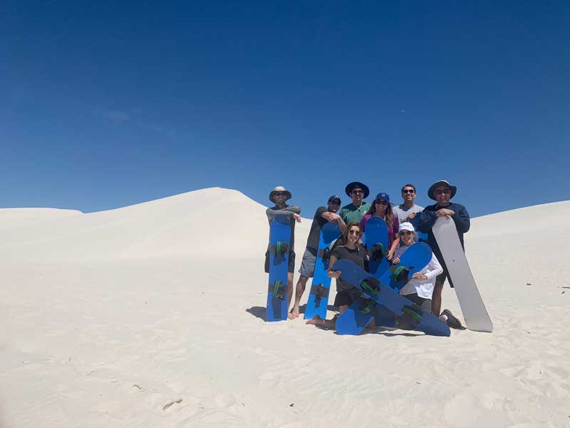Oscar Munoz And His Family Posing For Photo With Snowboard In Desert