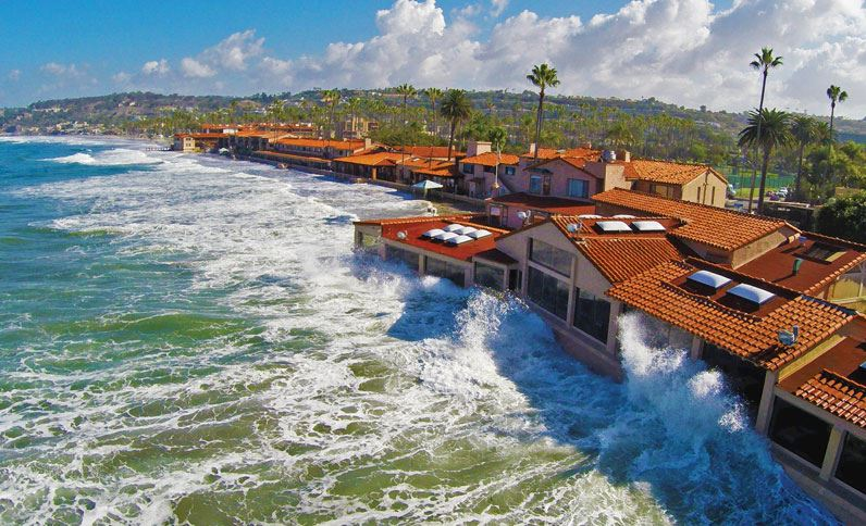 Sky View Of Marine Room On A Sunny Day With Waves Crashing Against Restaurant Windows