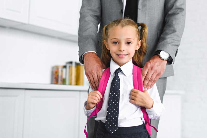 Little Girl with School Back Pack Smiling with Fathers Hands On Her Shoulders