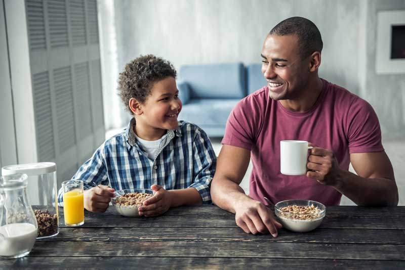 Black Father And Son Sharing A Breakfast And Smiling
