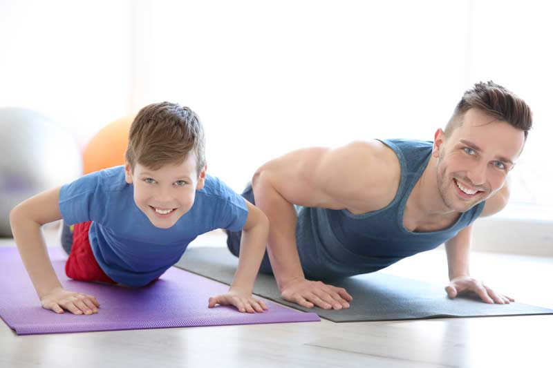 White Father And Son Smiling While Exercising Together