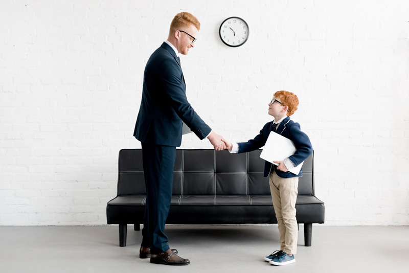 Business Man Shaking Hand With His Son Dressed Like Him