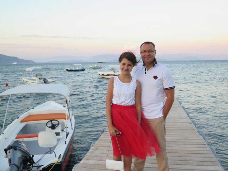 Vasyl Myroshnychenko With Daughter Standing On Dock By Water In Western United States
