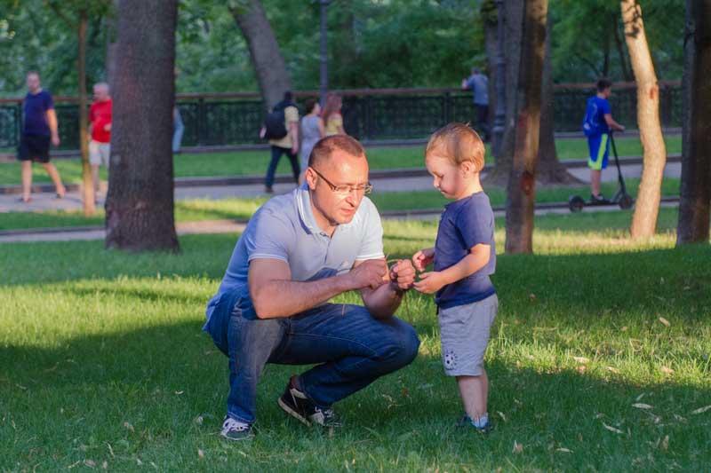 Vasyl Myroshnychenko Kneeling And Shaking To His Son Yuriy In Park