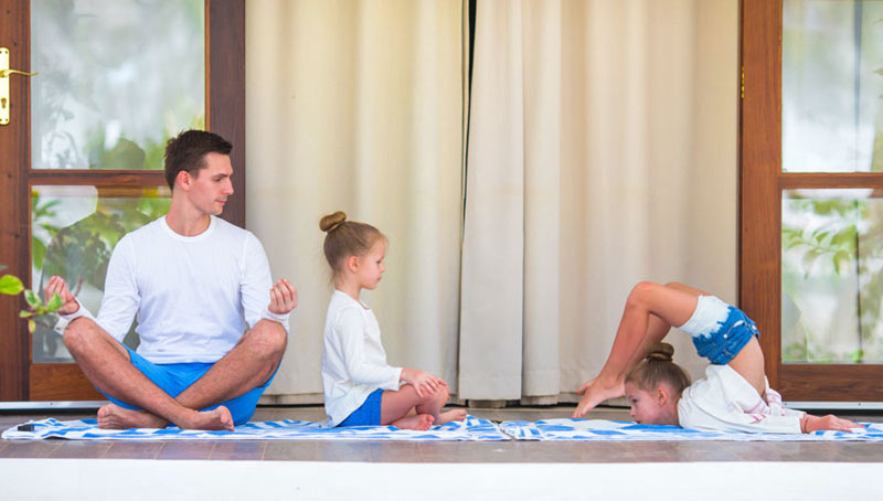 Father Looking At 2 Daughters While Doing Yoga
