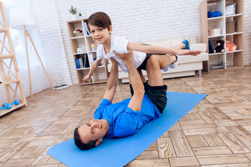 Father Holding Doing Yoga Exercise Together